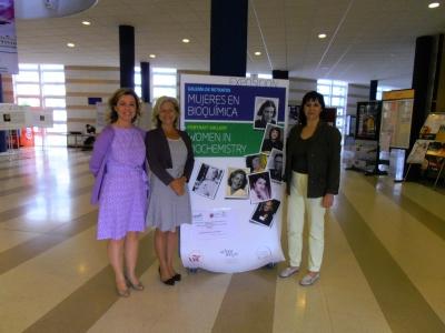 De izq.  a dcha. Maria Dolores Calzada, Carmen Galán  y  Gloria Priego ante el cartel de la exposición.