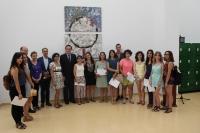 El rector junto a los participantes del concurso que posan delante de la obra ganadora del primer premio