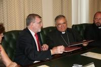 El rector y el obispo intercambian ejemplares del convenio firmado