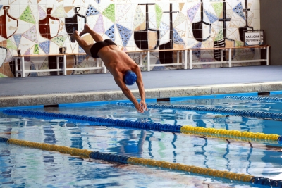 Detalle de la piscina con nadador al frente y su característico fondo de azulejos al fondo.