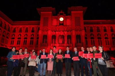 Las autoridades ante el Rectorado iluminado en rojo