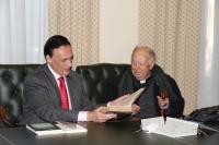 El rector, José Carlos Gómez Villamandos, recibe de manos de Álvaro Huerga, el volumen más antiguo de la donación.