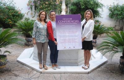 De izquierda a derecha, María Rosal, Ana María Guijarro y Rosario Mérida con el cartel anunciador del ciclo.