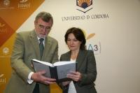 El rector y Celia Fernández hojean uno de los volúmenes antes de la presentación