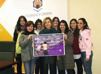 En el centro, la directora de la Unidad de Igualdad, Rosario Mérida, con mujeres universitarias y cartel conmemorativo del 8-M