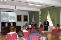 Rafael Jordano ( de pie) durante la presentación del libro. Al fondo las dos fotos que lo inspiran.