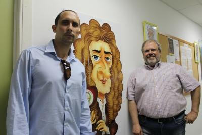 Óscar Reyes (i) y Sebastián Ventura junto a una caricatura de Isaac Newton expuesta en el Departamento de Ciencia de la Computación e Inteligencia Artificial de la UCO