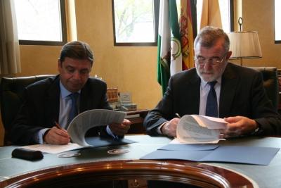 El consejero y el rector, en el momento de la firma