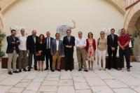 Equipo de investigación Antiguas Ciudades de Andalucía, de la UCO, junto a las autoridades, en la presentación de tres estatuas sedentes romanas en Baena, al fondo