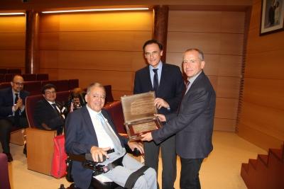 El rector y el decano del centro entregan la placa de reconocimiento a Enrique Aguilar Gavilán, uno de los profesores jubilados